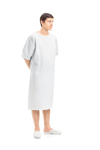 Full length portrait of a male patient in a hospital gown looking_ isolated on white background