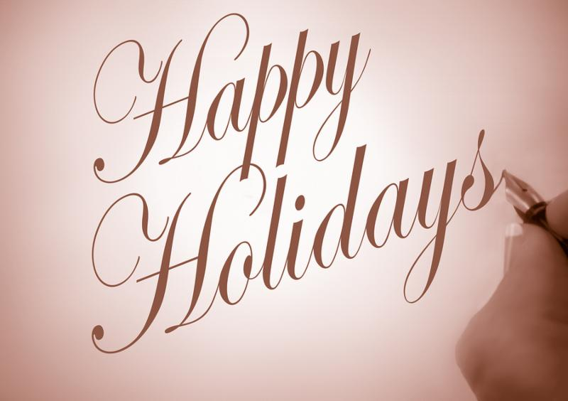 Person writing Happy Holidays in calligraphy script with sepia tone