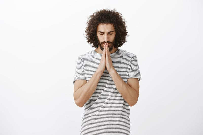 Portrait of focused believing hispanic guy with beard and afro hairstyle_ closing eyes_ holding hands in pray near mouth while praying or hoping_ talking to god_ standing over gray background.