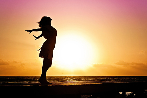 Photo of a woman silhouetted against a sunset
