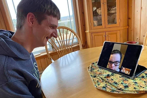 A man communicating with another on a video call
