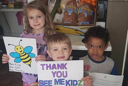 Image description. Three young children hold signs for Bee Me Kidz