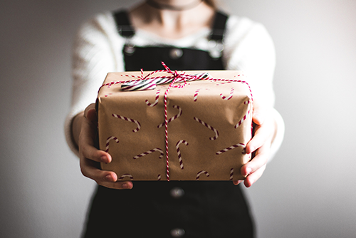 A child holding out a wrapped gift