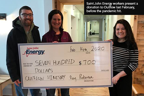 Saint John Energy employees present a donation cheque to Outflow