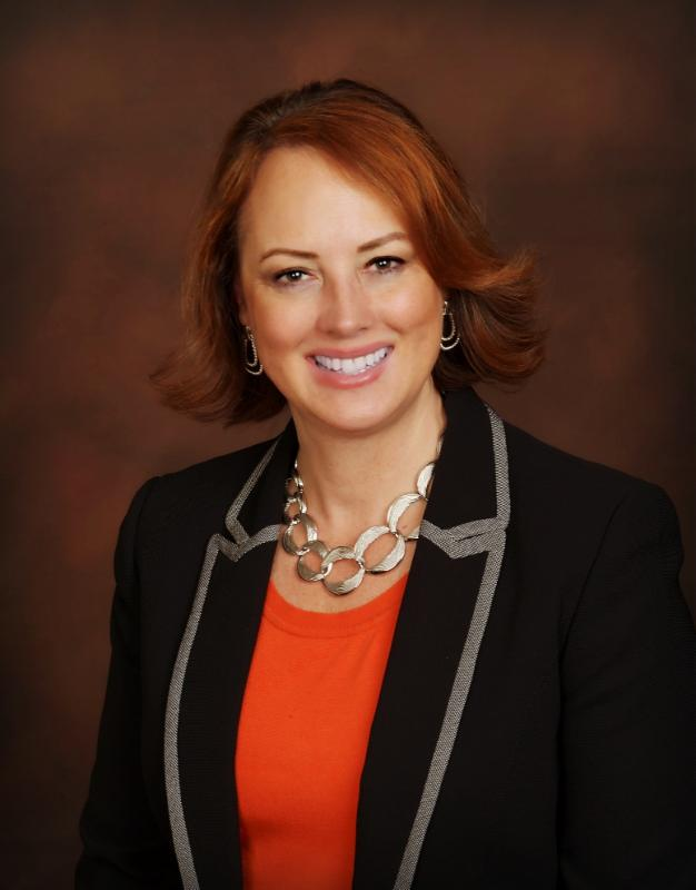 Woman with short brown hair and an orange in shirt and in a blazer smiling