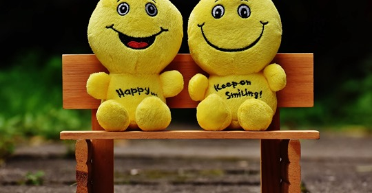 two smiling dolls on a bench