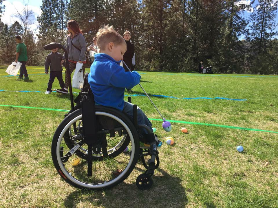 a boy in a wheelchair uses assistive technology to pick up an egg