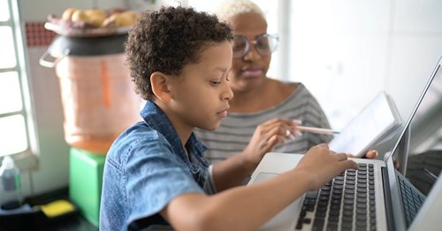 A child and a woman looking at a laptop