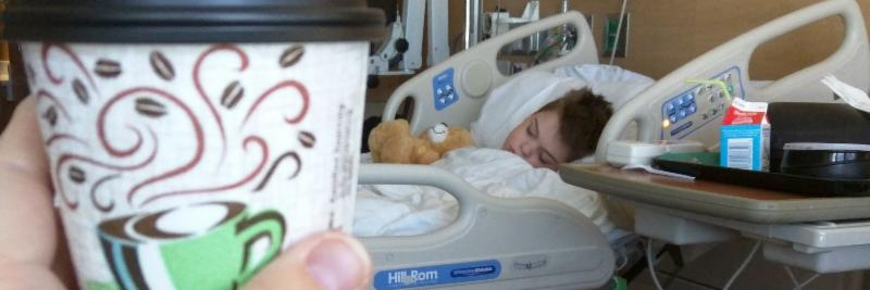 a cup of coffee held up in front of a child in a hospital bed