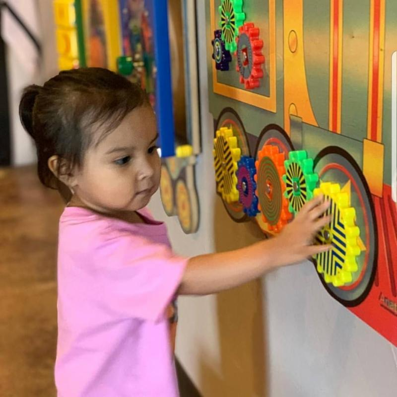 A young girl touches gears mounted on a wall