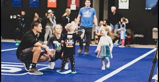 kids playing on the blue turf and helped by adults