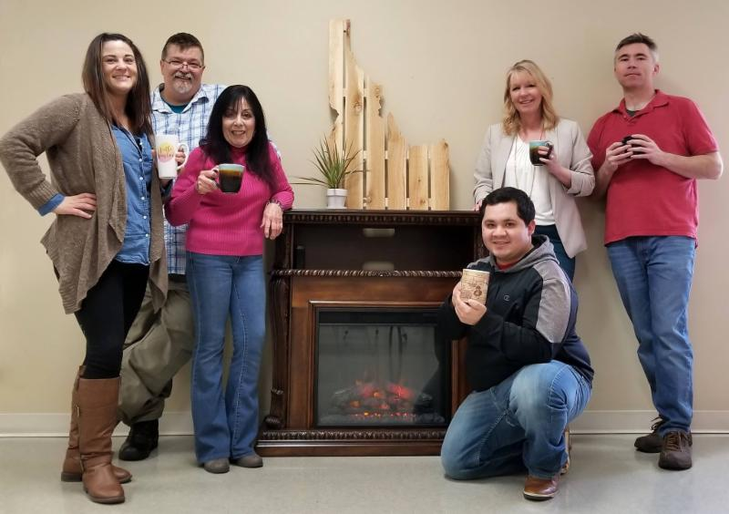 IPUL staff L to R Sarah Bill Candace Joe Angela and Casey all gather around a fake fireplace holding mugs of cocoa