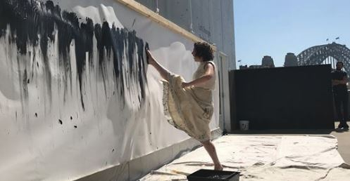 Prue Stevenson painting a wall with her feet
