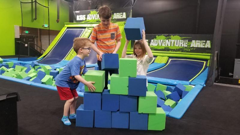 Three children stack foam blocks in front of trampoline pits
