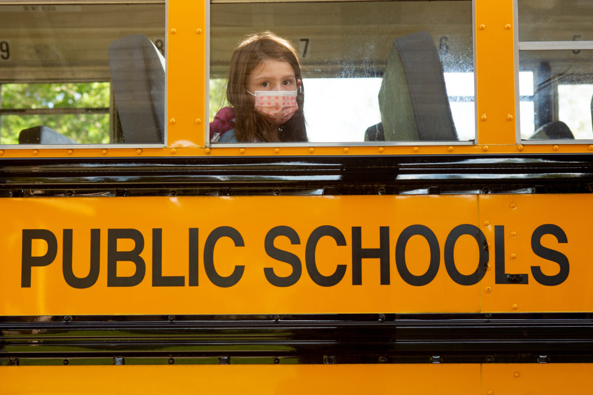 A student in a mask looks out of a bus window