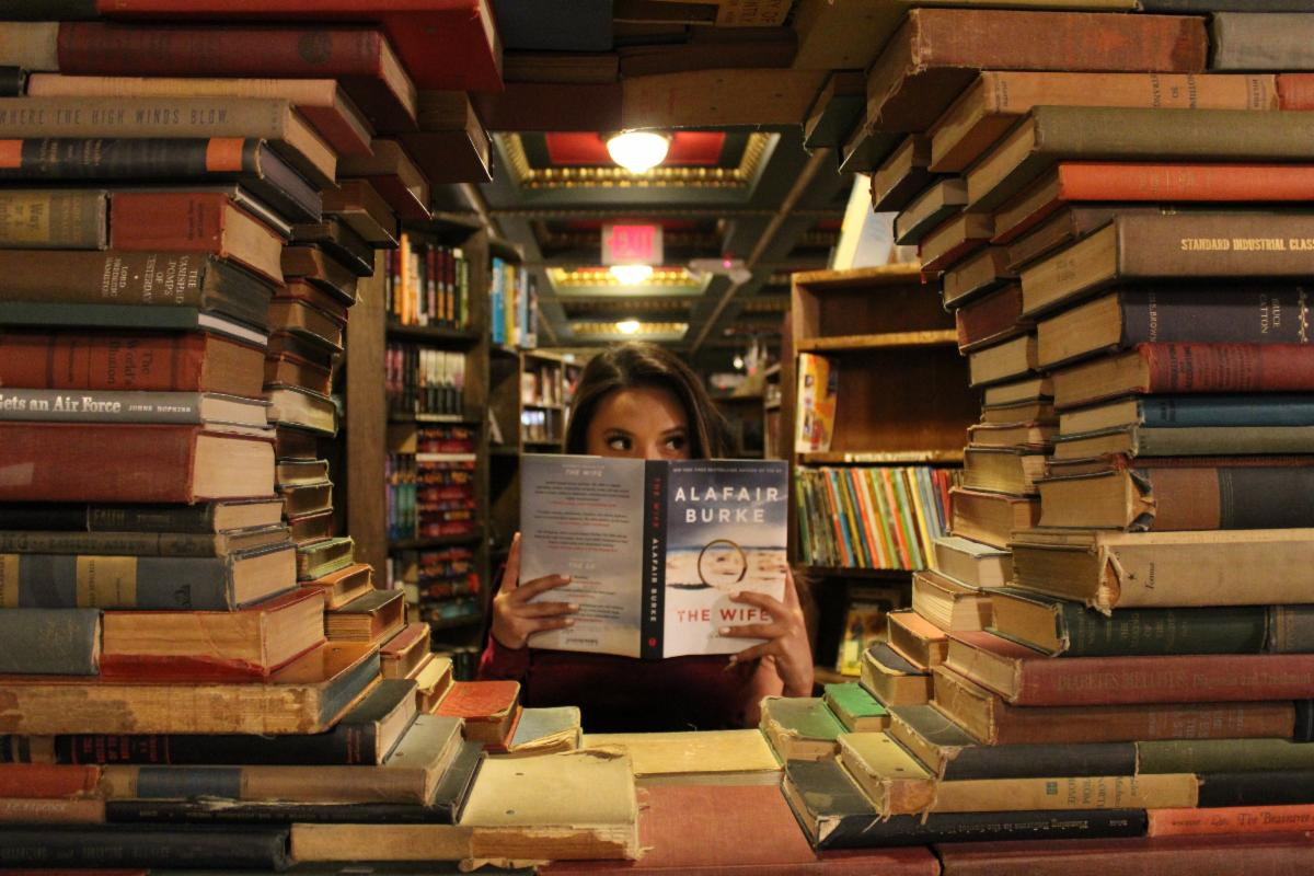 Woman peeks over a book in a library surrounded by books