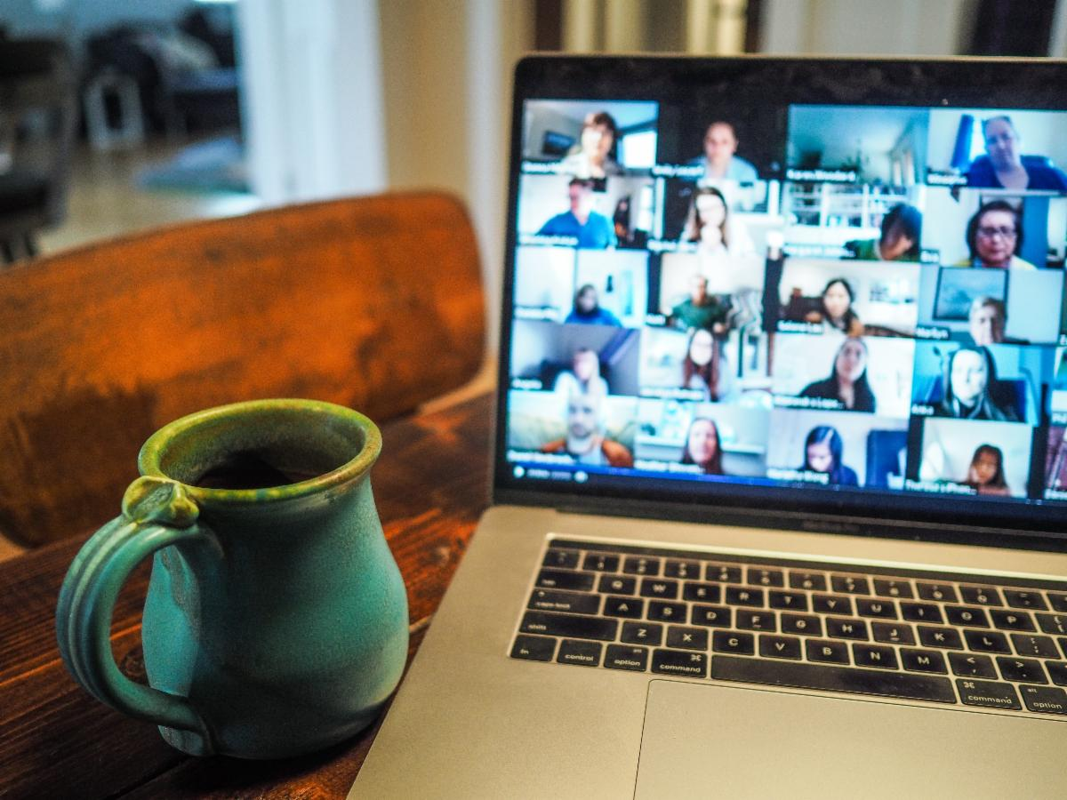 Computer with screen showing a web conference and a coffee mug nearby
