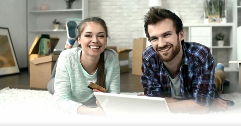 smiling man and woman on bed with open laptop