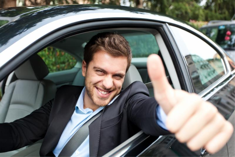 Caucasian man in car giving thumbs up
