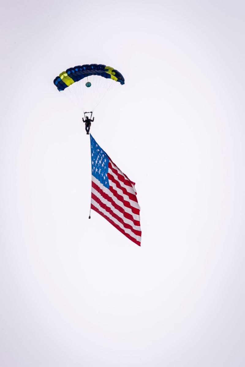 A member of the U.S. Parachute team arrives with the American flag during the singing of the National Anthem.