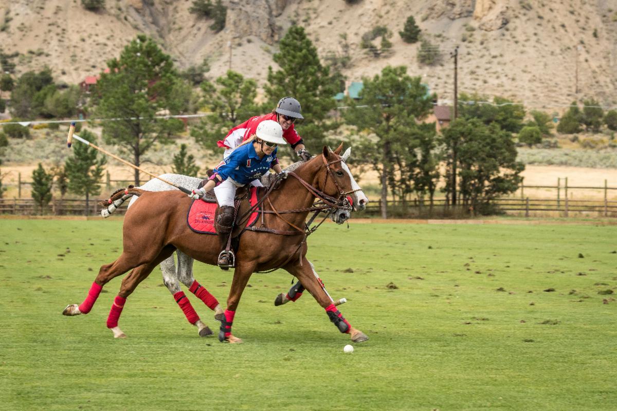 Alejandra Foster of Los Amigos Blue drives downfield with Tincho Merlos of Los Amigos Red on her hip defending.