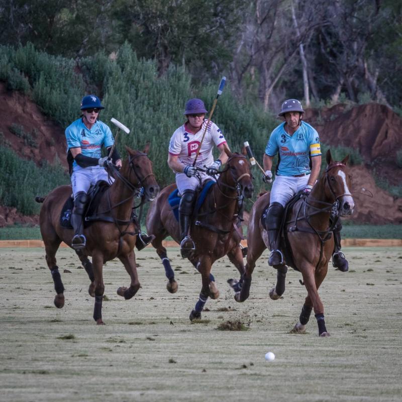 Casablanca teammates Juancito Bollini and Nacho Novillo Astrada surround Kris Kampsen of McClure River Ranch.