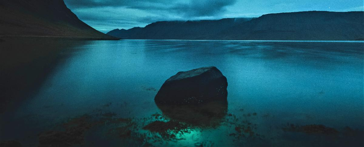 A rock stands alone in the middle of a night-shrouded lake. The sky above glows with the northern lights, which reflect off the water below.
