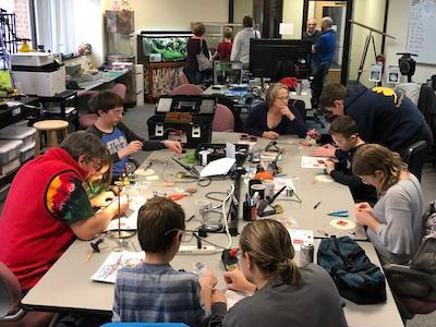Photo: kids and adults soldering projects in the maker space