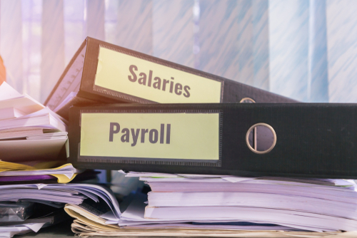 Payroll and salaries folders stack with label on black binder on paperwork documents summary report_ HR-human resources business and bookkeeping accountancy concept in busy offices