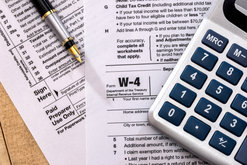 tax form 1120 with calculator and pen