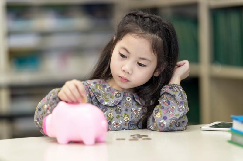 Selective focus at pig jar. Kids playing collect money with a pink saving Pig Jar in the Library. Setup studio shooting.