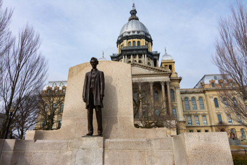 Statue of Abraham Lincoln and State Capitol Building on a Spring morning.  Springfield_ Illinois_ USA.