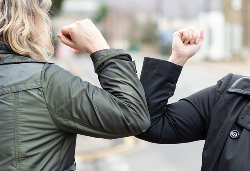 Elbow bump. New novel greeting to avoid the spread of coronavirus. Two women friends meet in a British street with bare hands. Instead of greeting with a hug or handshake_ they bump elbows instead.