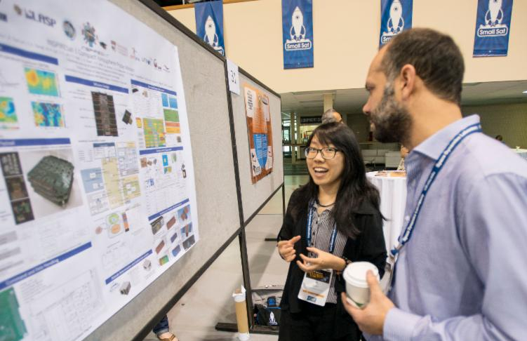 Student explains University research displayed at the Small Satellite Conference Poster Session