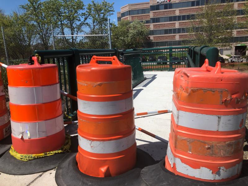 Image of 3 orange and whte barrels blocking the entrance to a ramp.  There is an office building in the background..