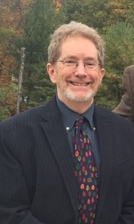 A white male with reddish grey hair_ wire rim glasses a whitish beard wearing a dark suit with a dark shir and a polka dotted tie