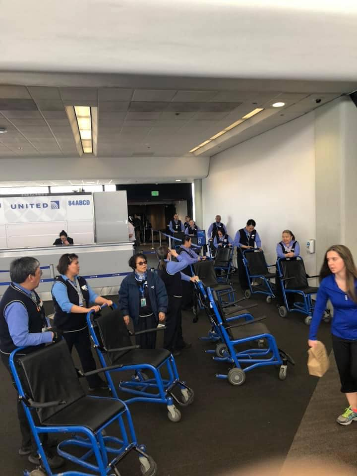 Picture of at least 10 airport workers with wheelchairs waiting at an airport gate.  Photo by Brendan Decker