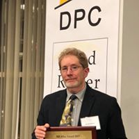 Man with red hair wearing a suit jacket and tie holding an award under a banner with the DPC logo.
