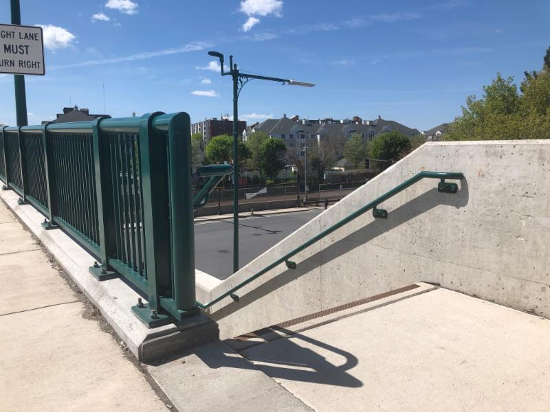 Image of the top of a cement staircase descending with a iron railing on the right.  To the left of the staircase is a green metal fence with a sidewak to the far left.