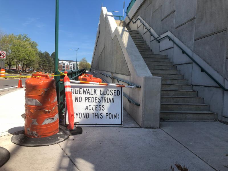 Picture on the right is a cement staircase with a metal railing on the right side.  On the left side of the magie is two orange and white cans tied to a lamppost. There is a ramp behind a white sign with black lettering that states _Sidewalk closed no pedestrian access beyond this point.
