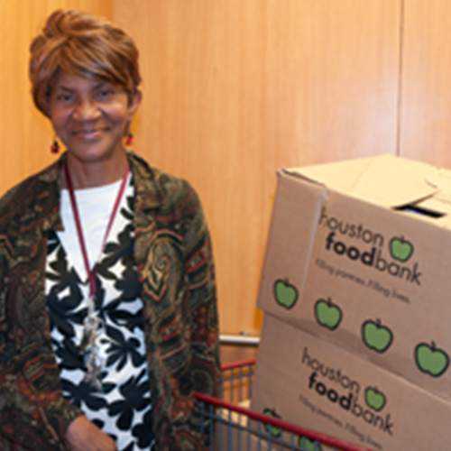 A senior woman smiles at the viewer while standing beside food bank boxes