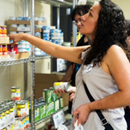 A woman browses shelves full of non-perishable foods