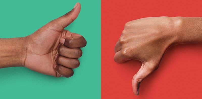 Collage of black hands showing thumb up and down at green and red background_ copy space. Approval and disagreement gestures. Mockup for survey or poll