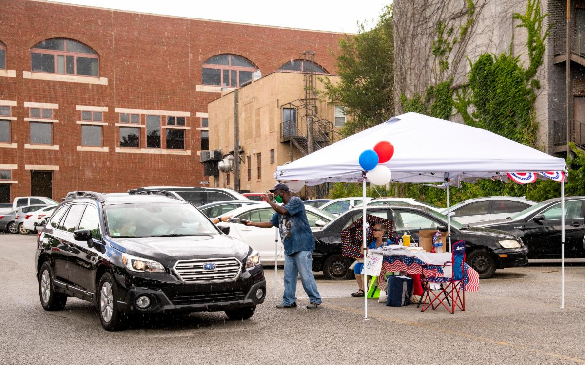 A car drives up to a canvasser stationed in a parking lot for a proposed 2020 ballot issue.