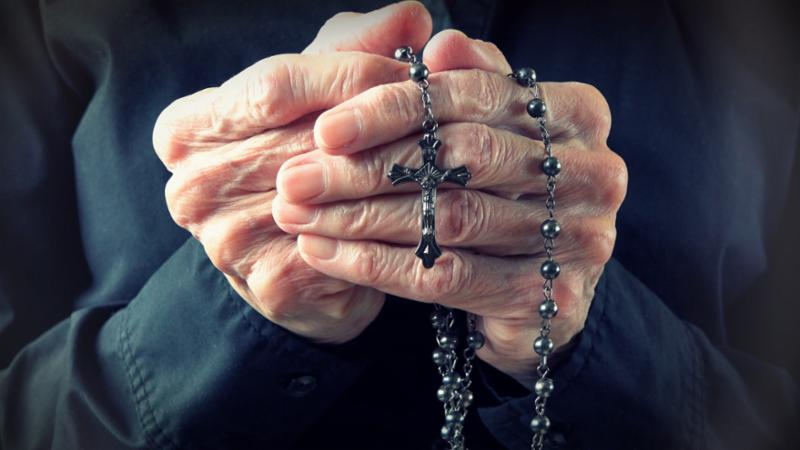 elder_woman_holding_rosary.jpg