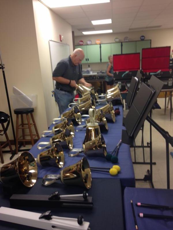 Ringer Sterling Smith polishing bass bells after practice