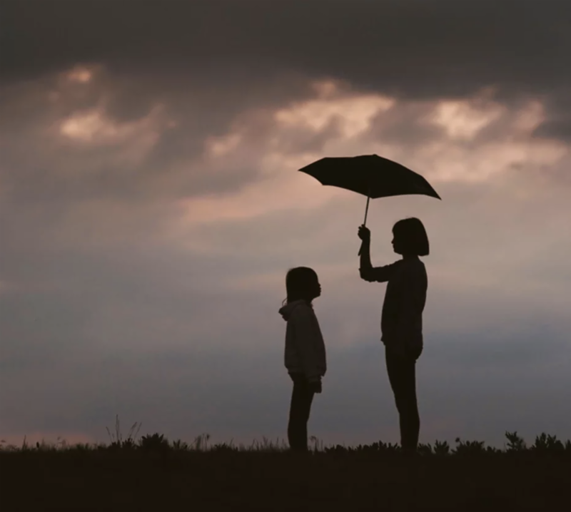 Silhouettes of child holding umbrella over other child outdoors on a field at dusk
