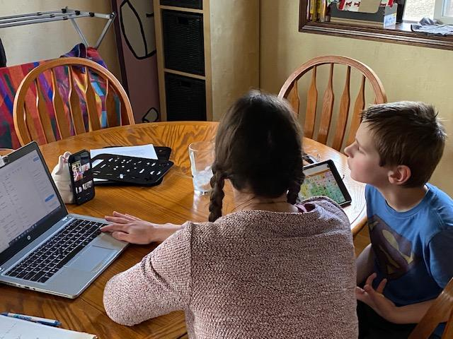Mother and son sitting at kitchen table looking at laptop and AAC device