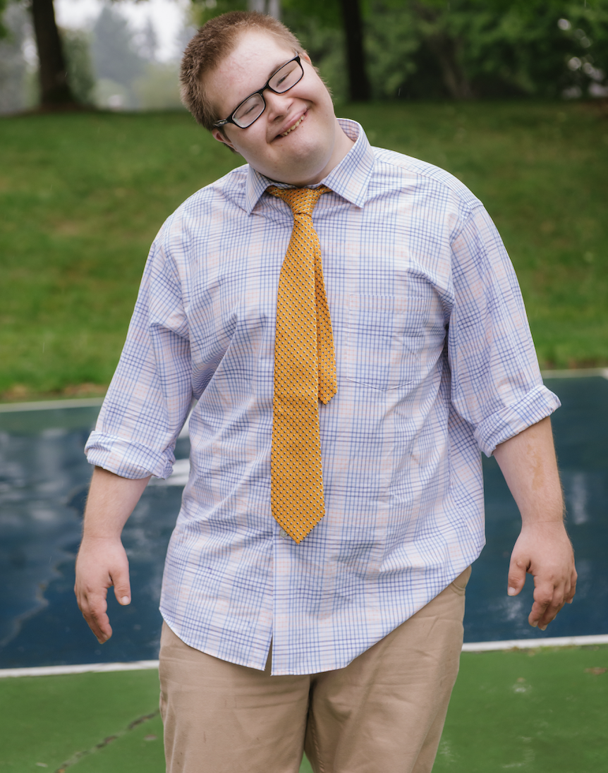 Boy wearing glasses and yellow tie and checkered shirt smiling outside on a basketball court