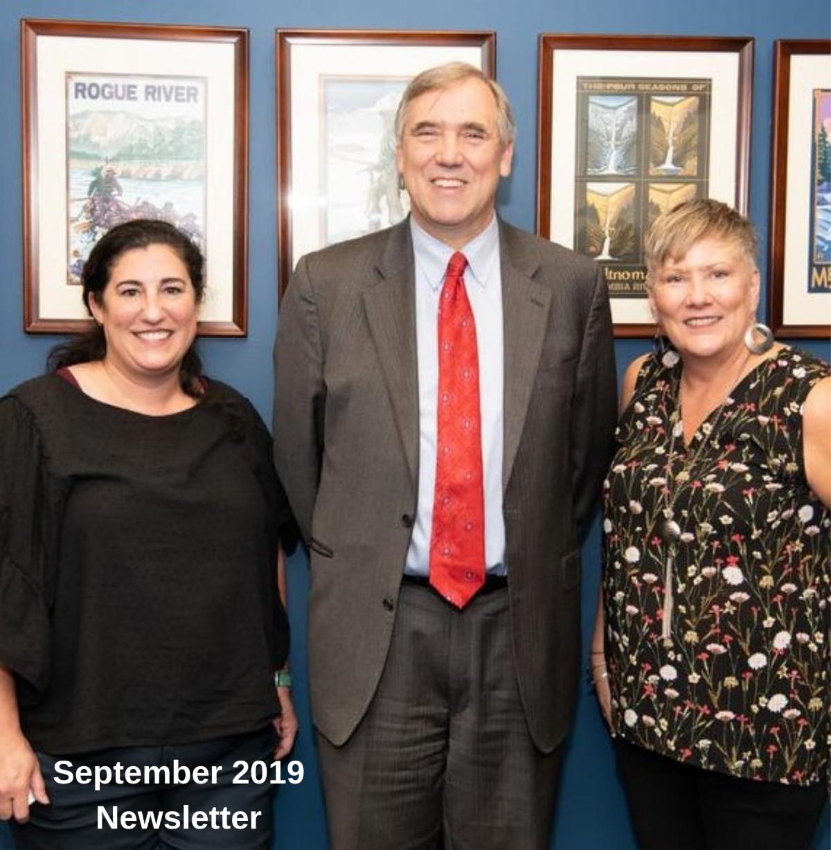 Executive Director Roberta Dunn and Program Coordinator Heather Olivier standing next to Senator Merkley